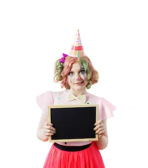 Sorria garota adolescente em traje de palhaço com placa de escrita isolada