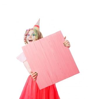 Sorria garota adolescente em traje de palhaço com placa de escrita