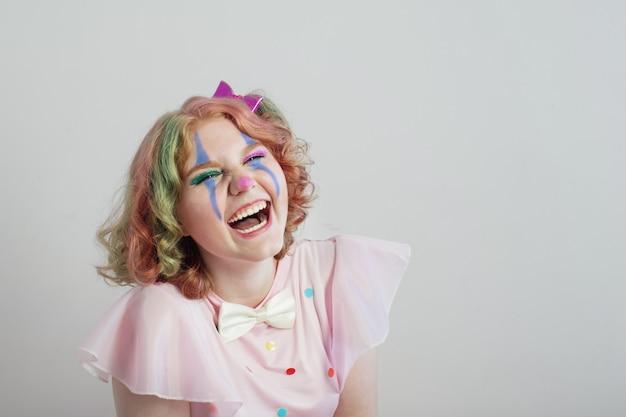 Sorria garota adolescente em traje de palhaço na superfície cinza