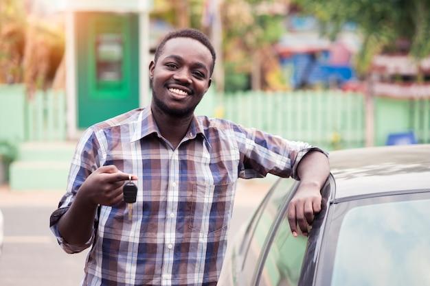 Sorria homem africano com as chaves no carro