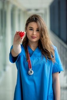 Sorria muito médica em uniforme azul com estetoscópio com coração. assistência médica