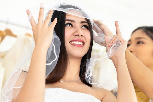 Sorria mulher asiática medindo no vestido de casamento em uma loja pelo alfaiate.