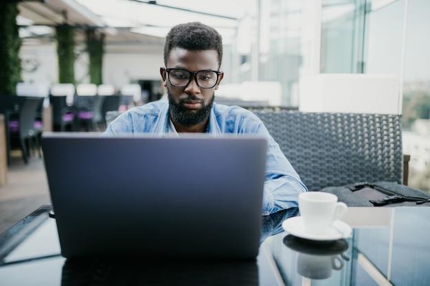Sorria o empresário africano sentado no café, segurando uma xícara de café e usando o laptop.
