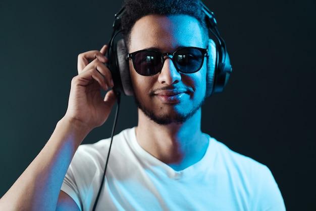 Sorria retrato de jovem afro-americano usando fones de ouvido e curta música sobre a parede preta