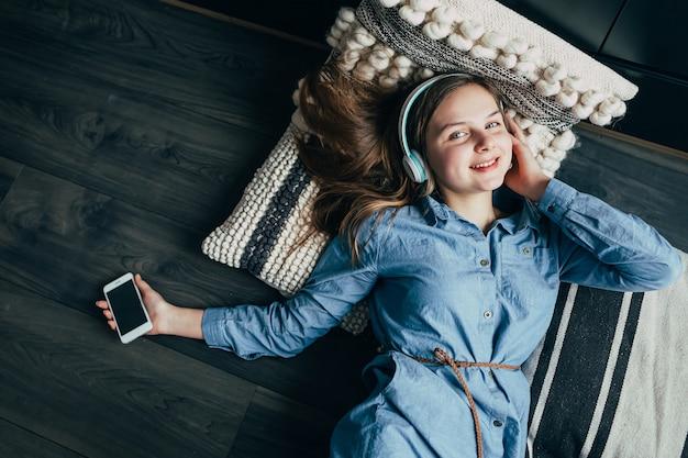 Sorridente adolescente deitado no chão, relaxando e ouvindo música no fone de ouvido