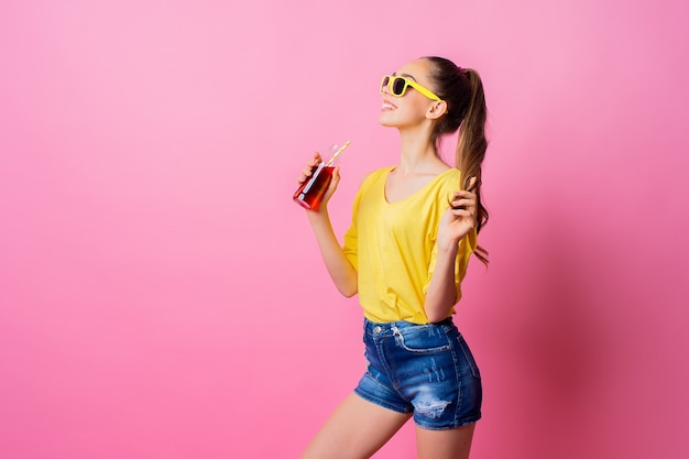 Sorridente adolescente em pé e beber bebidas com palha
