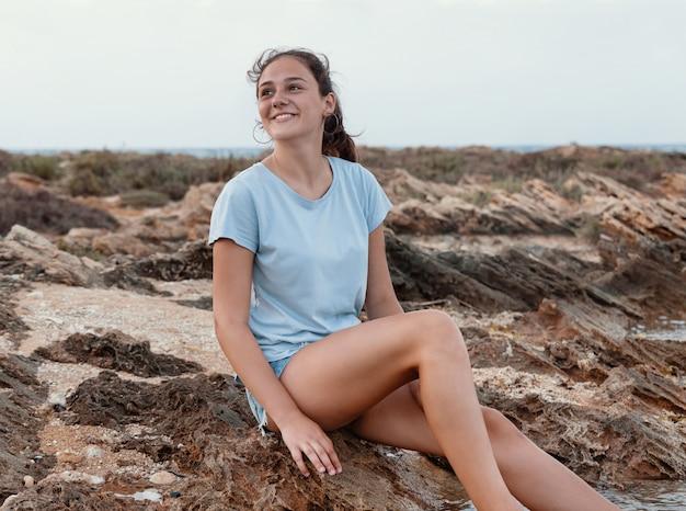 Sorridente adolescente sentada na falésia à beira-mar com as pernas na água ao pôr do sol e olhando para cima, vestindo camiseta azul e shorts jeans. maquete de camiseta