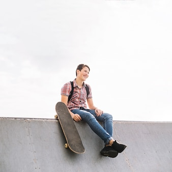 Sorridente adolescente sentado na rampa