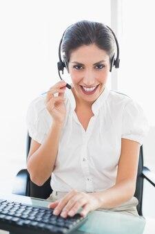 Sorridente agente do call center trabalhando em sua mesa em uma chamada
