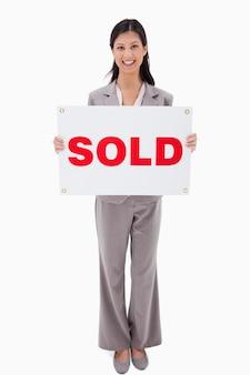 Sorridente agente imobiliário com sinal vendido