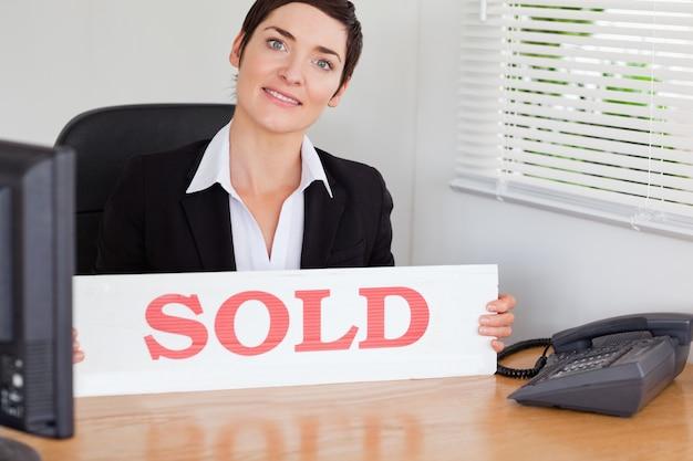Sorridente agente imobiliário com um painel vendido