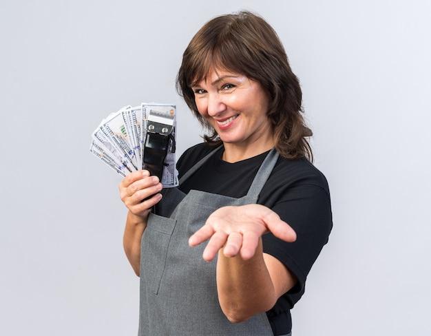 Sorridente barbeira adulta de uniforme segurando o aparador de cabelo com dinheiro e mantendo a mão aberta, isolada na parede branca com espaço de cópia