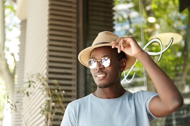 Sorridente bonitão americano africano jovem vestindo máscaras de lentes espelhadas redondas, ajustando seu chapéu bege, tendo um olhar despreocupado e feliz, esperando seu almoço enquanto relaxa na cafeteria ao ar livre