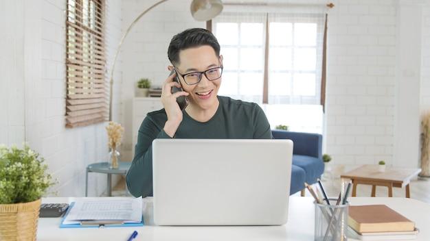 Sorridente bonito empresário asiático trabalhando remotamente de casa. ele está falando ao celular.