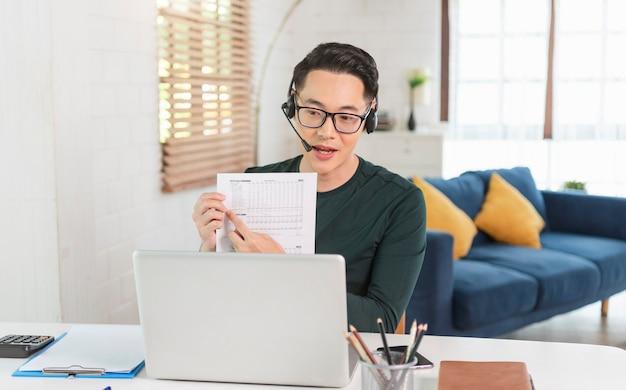 Sorridente bonito empresário asiático usa fones de ouvido trabalhando remotamente de casa. ele é uma videoconferência webinar