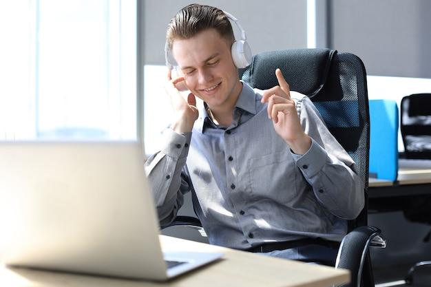 Sorridente bonito empresário relaxante e ouvindo música em fones de ouvido em um escritório moderno.