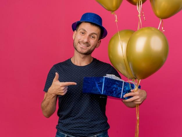 Sorridente, bonito homem caucasiano com chapéu de festa azul aponta e aponta para balões de hélio isolados em um fundo rosa com espaço de cópia