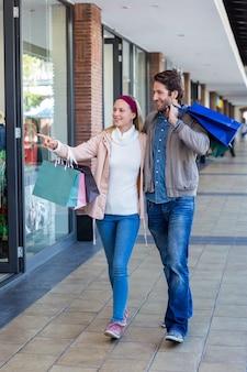 Sorridente casal andando de mãos dadas e indo às compras na janela