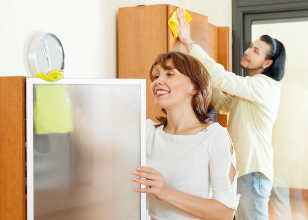Sorridente casal de limpeza em casa