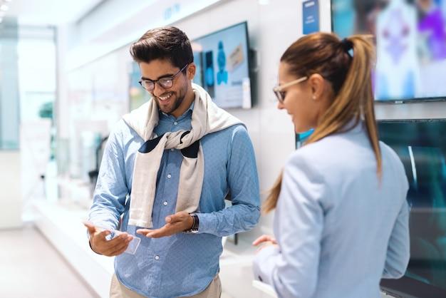 Sorridente casal multicultural fofo em pé na loja de tecnologia e pelo preço da nova televisão que eles querem comprar