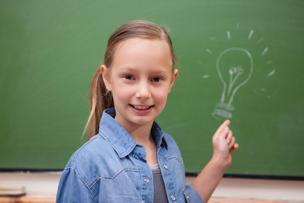 Sorridente colegial apontando para uma lâmpada