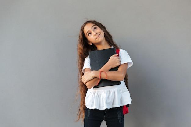 Sorridente colegial morena pensativa com cabelos longos, abraçando o livro