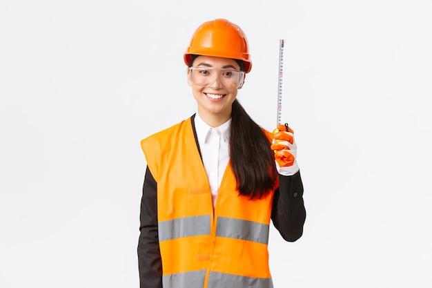 Sorridente confiante, engenheira profissional asiática, técnica de construção com capacete de segurança e uniforme reflexivo, em pé com fita métrica, layout de medição na área de construção