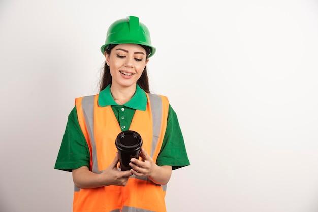 Sorridente construtor feminino olhando na xícara preta. foto de alta qualidade