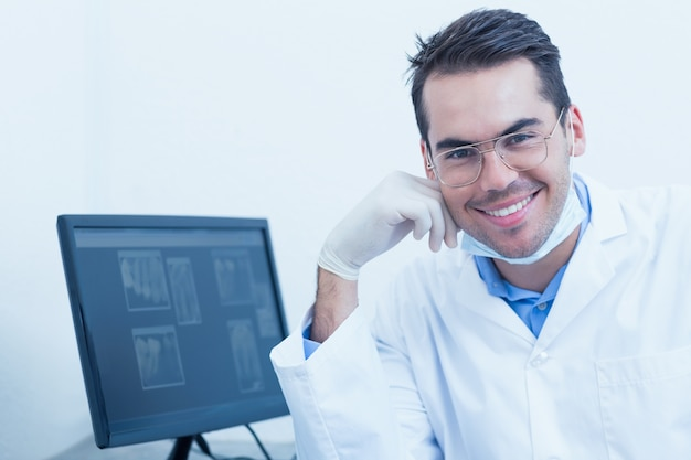 Sorridente dentista masculino com computador