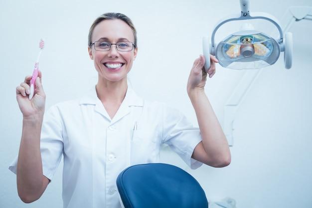 Sorridente, dentista, segurando, escova de dentes