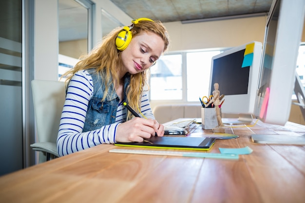 Sorridente designer trabalhando com digitalizador e ouvindo música