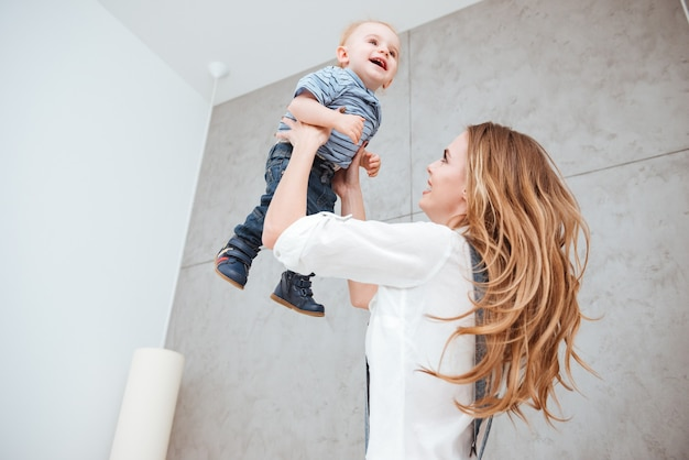 Sorridente e alegre jovem mãe brincando e se divertindo com seu filho pequeno em casa
