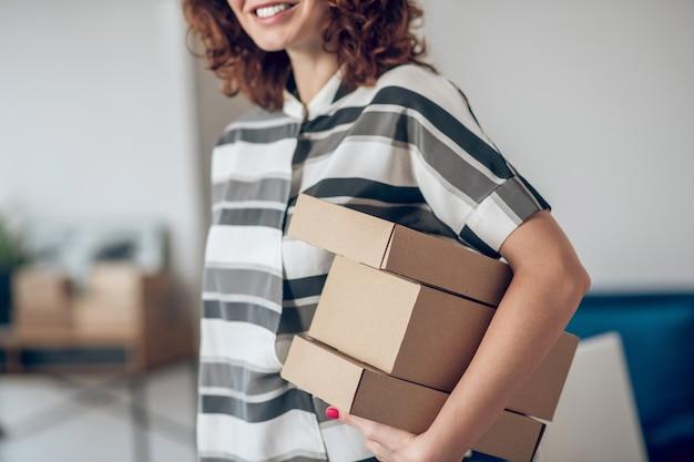 Sorridente e alegre trabalhadora com pacotes em pé