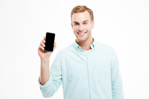 Sorridente e atraente jovem empresário segurando um smartphone com tela em branco sobre uma parede branca