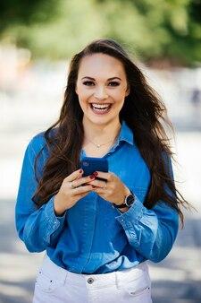 Sorridente e bela mulher urbana usando smartphone na rua