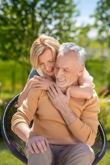 Sorridente e bonito homem de cabelos grisalhos sentado na poltrona abraçado por sua esposa por trás