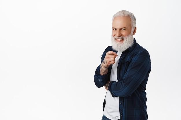 Sorridente e bonito homem sênior com barba comprida, apontando o dedo para a frente e parecendo feliz, escolhendo, convidando ou recrutando pessoas, elogiando uma pessoa, em pé sobre uma parede branca