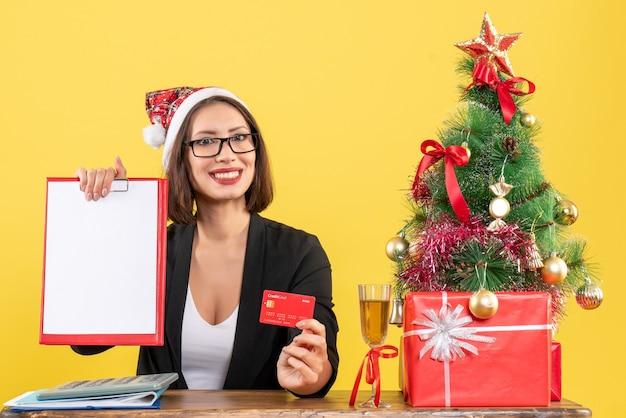 Sorridente e encantadora senhora de terno com chapéu de papai noel e óculos mostrando o cartão do banco e o documento no escritório em amarelo isolado