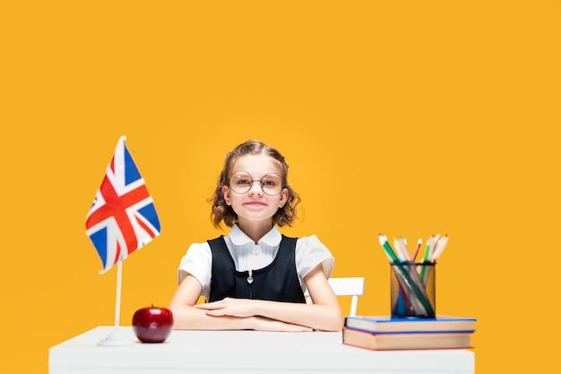 Sorridente e feliz aluna caucasiana sentada na mesa durante a aula de inglês. bandeira da grã-bretanha