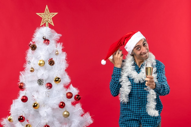 Sorridente e feliz rapaz brincando com chapéu de papai noel, erguendo uma taça de vinho e segurando o relógio perto da árvore de natal no vermelho
