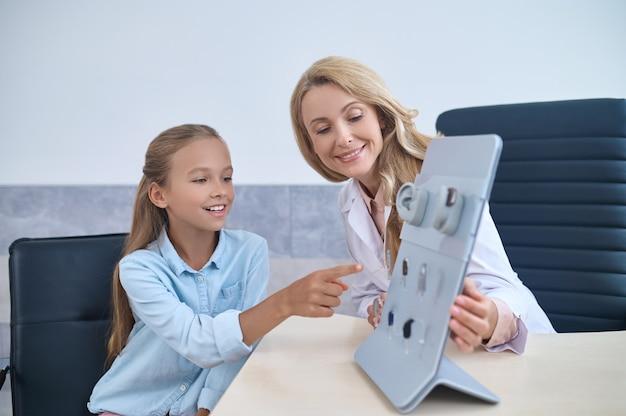 Sorridente e fofa garota caucasiana focada em escolher um aparelho de escuta assistida por uma experiente e amigável médica de meia-idade