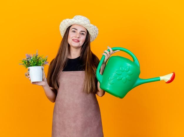 Sorridente e linda menina jardineira vestindo uniforme e chapéu de jardinagem segurando um regador com flores em flwerpot isolado em fundo laranja