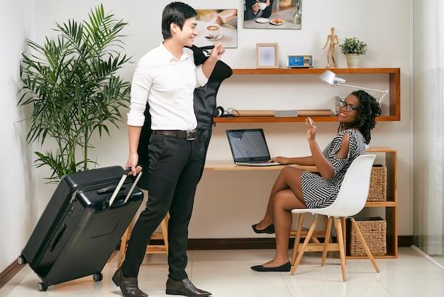 Sorridente e linda negra empreendedora de óculos acenando para um colega com uma mala e uma capa para uma viagem de negócios