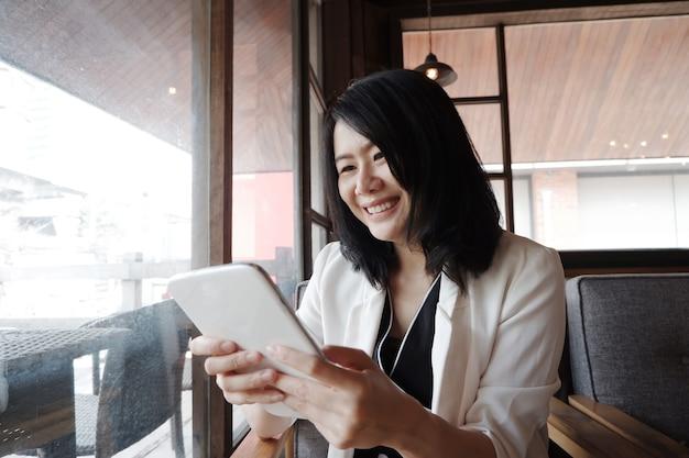 Sorridente empresária asiática está segurando o tablet para fazer compras online nas mídias sociais no local de trabalho em um escritório moderno ou relaxar no café. estilo de vida das pessoas com o conceito de tecnologia.