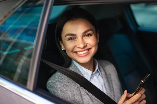 Sorridente empresária com smartphone no carro