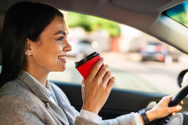 Sorridente empresária dirigindo e tomando café