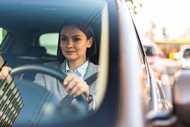 Sorridente empresária dirigindo o carro dela