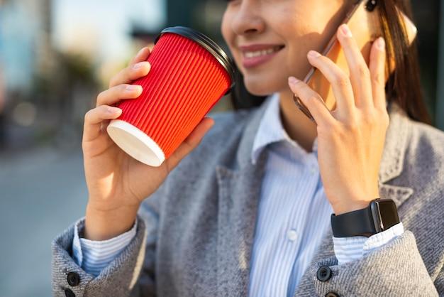Sorridente empresária falando ao telefone enquanto toma um café lá fora