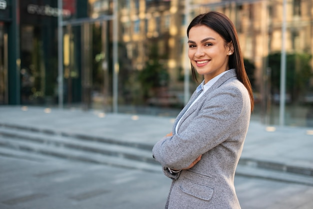 Sorridente empresária posando ao ar livre com os braços cruzados