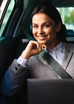 Sorridente empresária posando no carro